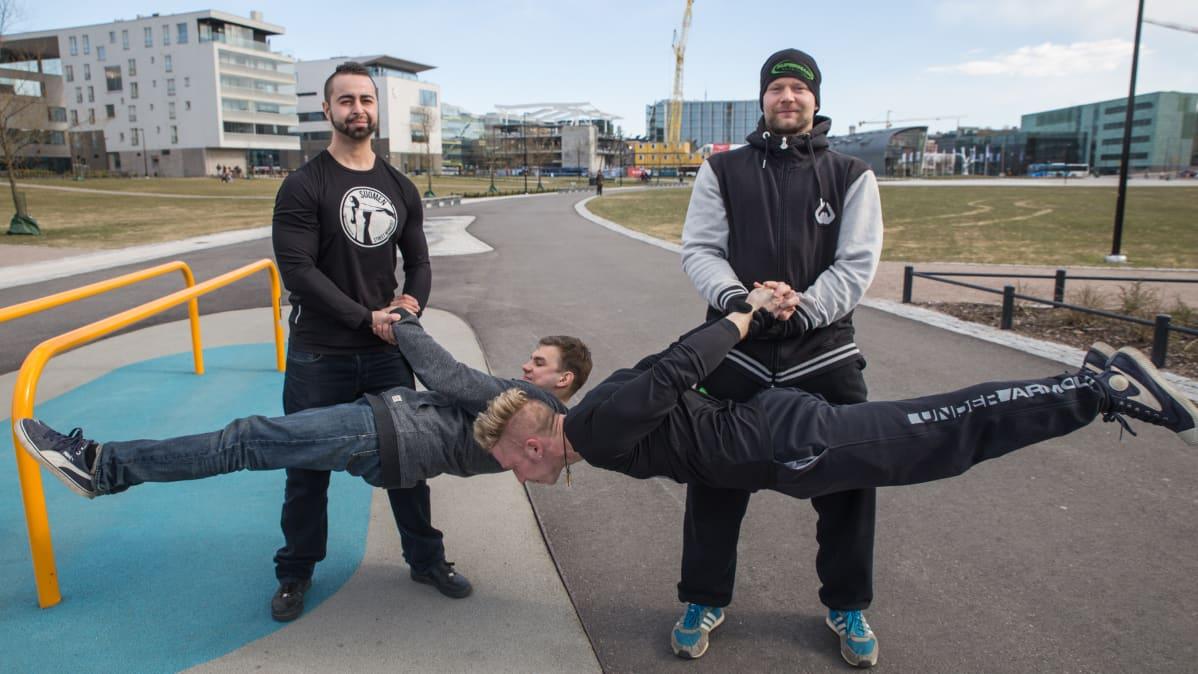 Kaksi miestä pitää kahta street workout treenaajaa ilmassa.