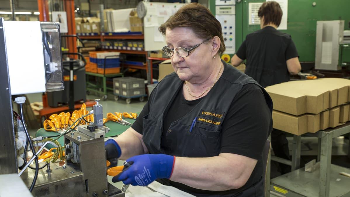 nainen kokoaa saksia