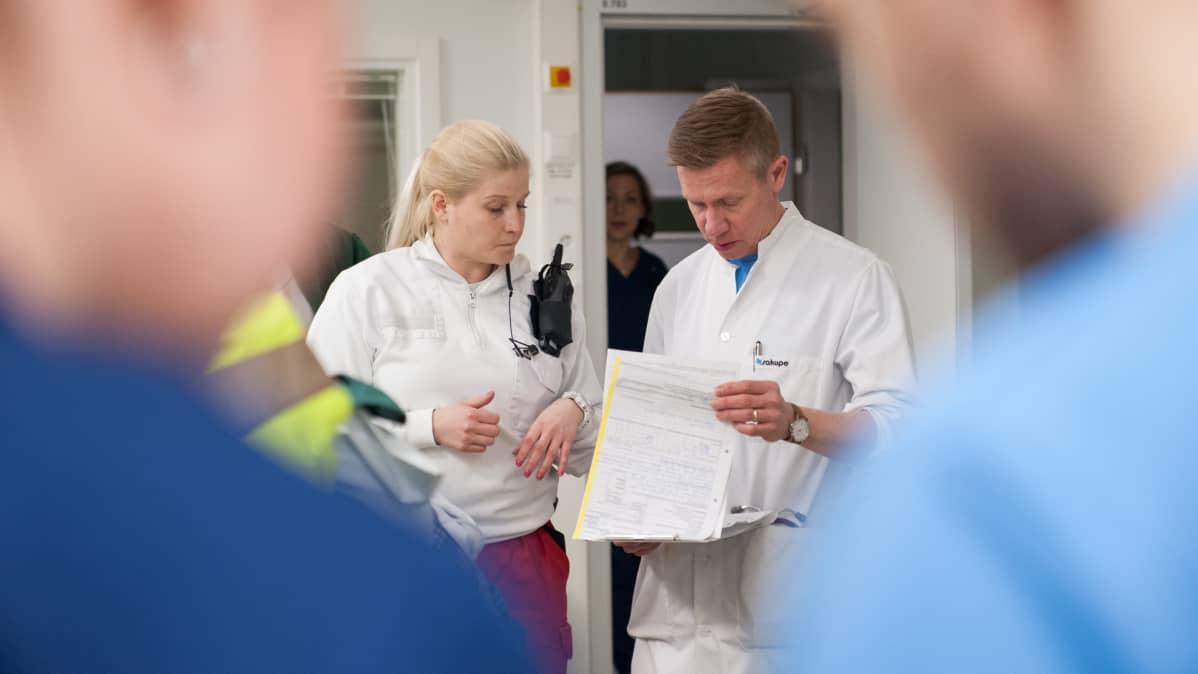 Ensihoitaja vaihtaa tietoja neurologin kanssa päivystykseen tuodusta potilaasta.