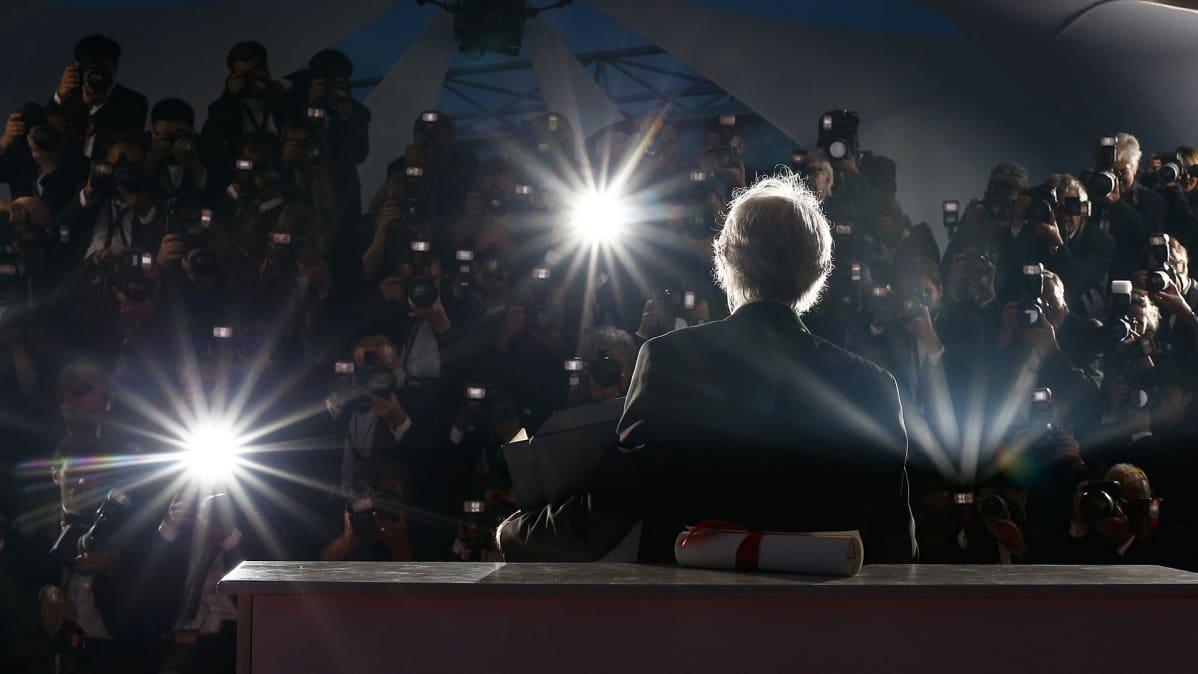 Kultaisella palmulla palkittu englantilaisohjaaja Ken Loach kuvattuna lehdistön ympäröimänä Cannesissa 22. toukokuuta 2016.