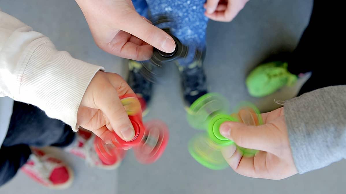 Kolme fidger spinneriä tyttöjen kädessä.