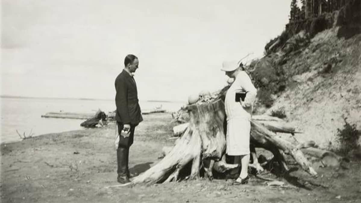 Mies ja nainen tarkastekevat järveen vyöryneen hatuausmaan paljastamia pääkalloja kannon päällä hiekkarannalla.