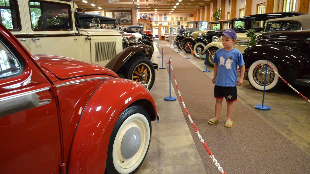 Poika katselee museoautoja Vehoniemen automuseossa.