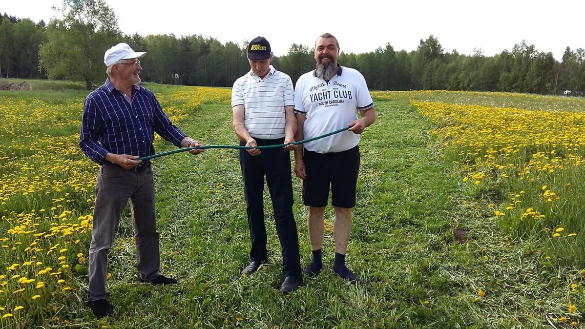 Kolme miestä mittailee letkunheiton MM-kisojen kisavälinettä