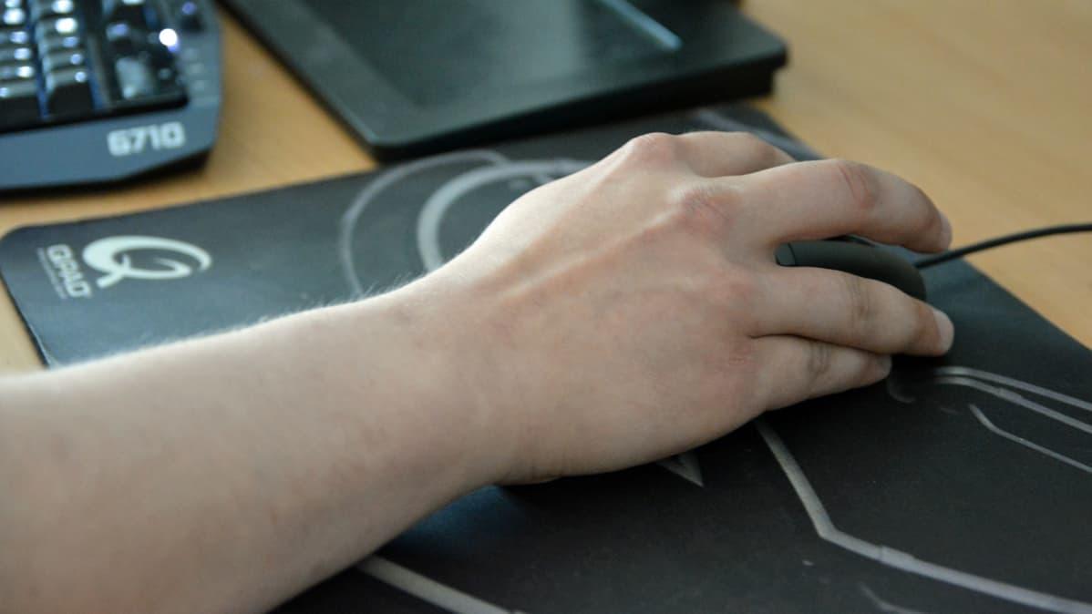 Käsi liikuttaa tietokoneen hiirtä.