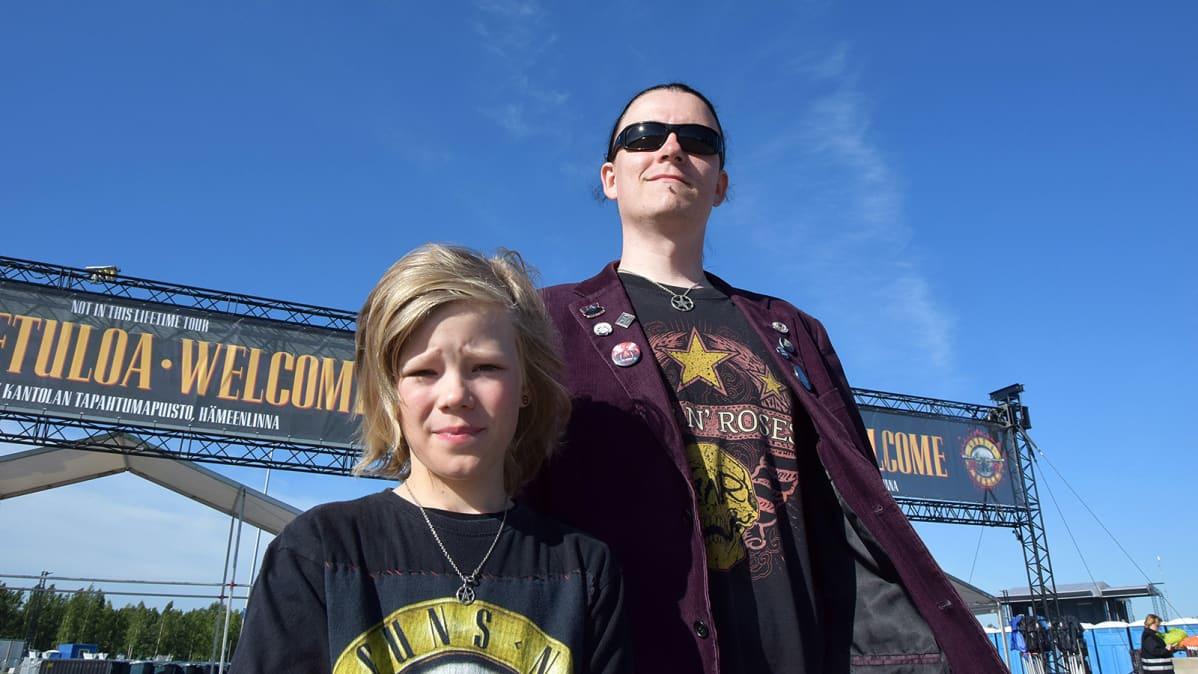 Isä ja poika Guns N' Rosesin keikkapaikan pääportin edessä