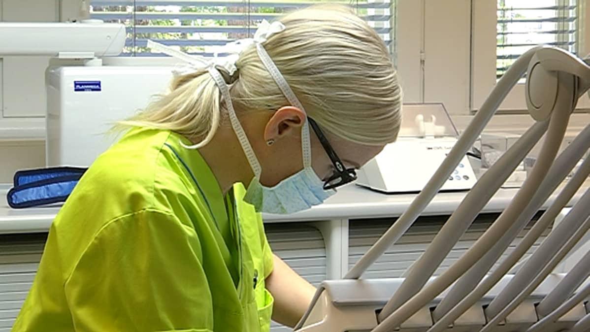 Hammaslääkäri Katri Hyvärinen hoitaa asiakkaan hampaita