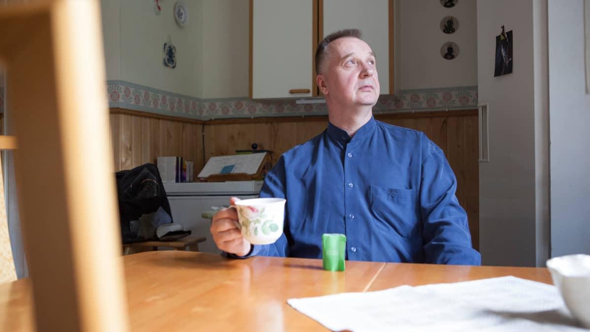 Matti Koskinen istuu keittiönpöydän ääressä juomassa teetä.