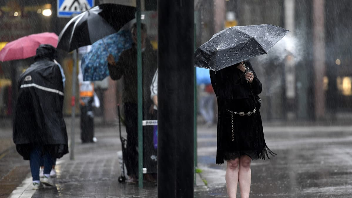 Ihmisiä sadesäässä bussipysäkillä Helsingissä 11. heinäkuuta.