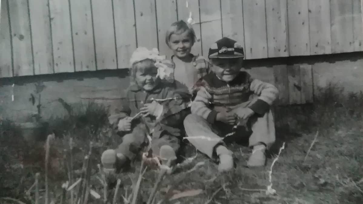 Kolme lasta istuu talon pihalla.