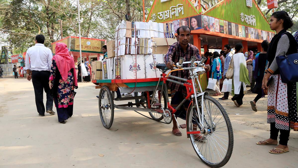 Mies kuljettaa kirjoja pyörällään Bangladeshin kirjamessuilla.