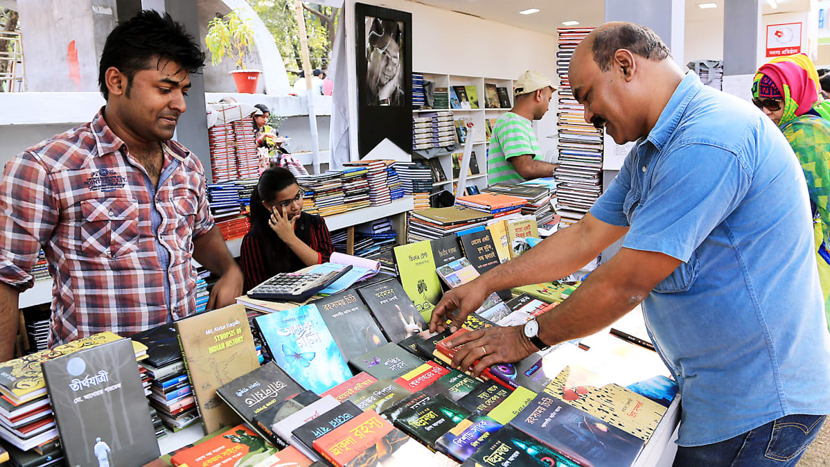 Asiakas katselee kirjoja Bangladeshin kirjamessuilla.