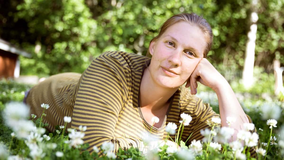 Mikaela Sundman makoilee nurmikolla.