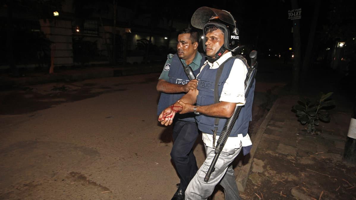 Poliisi saattoi haavoittunutta kollegaansa pommi-iskun jälkeen.