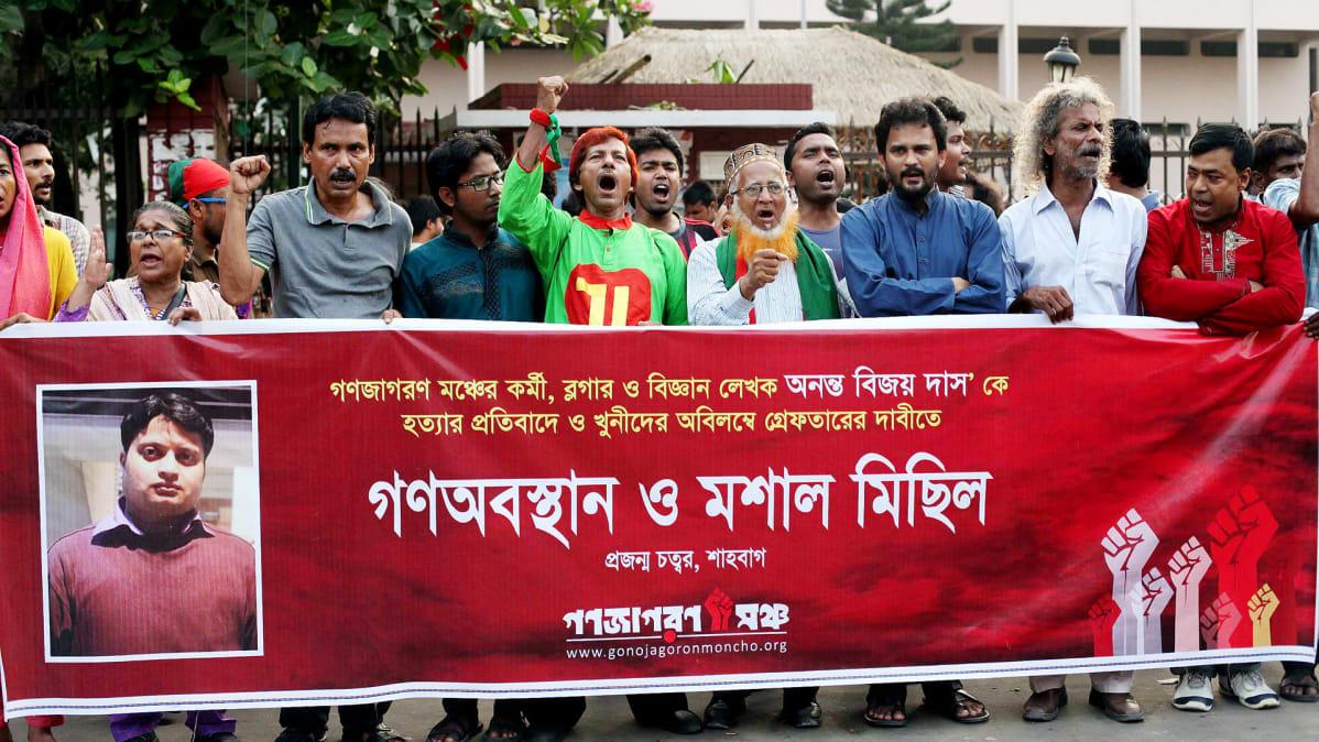 Mielenosoittajia, edessä iso banneri ja  Ananta Bijoy Dasin valokuva.