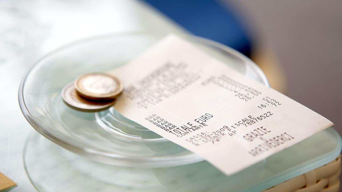 Pöydällä lautasella on kuitti ja juomaraha euroina.