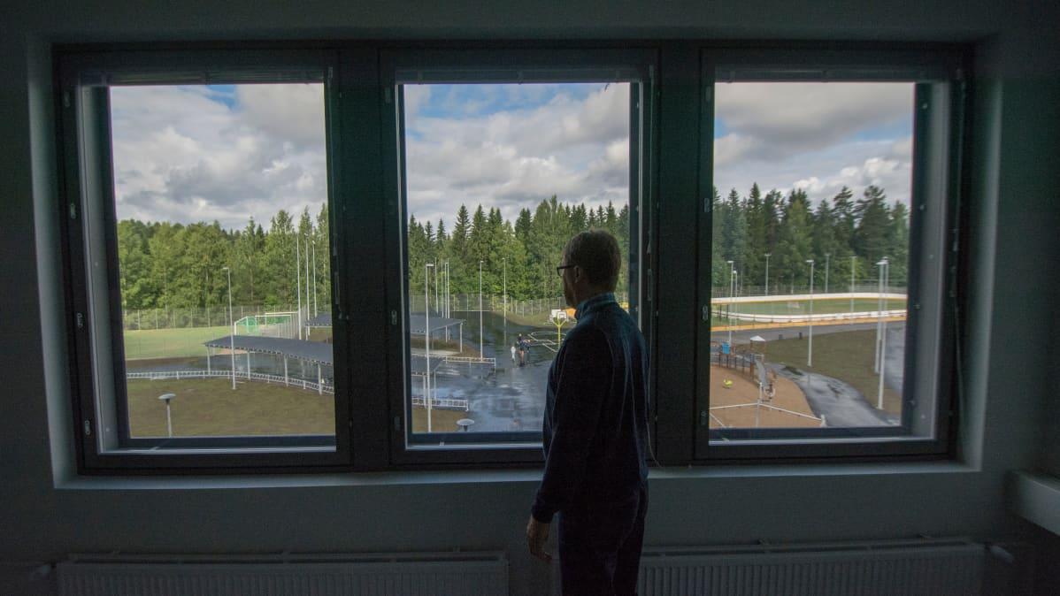 Rehtori katsoo ikkunasta.