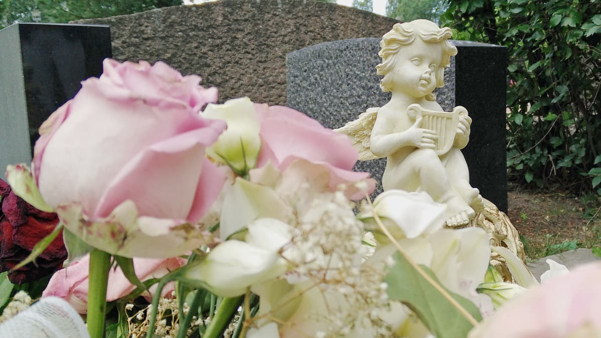 Pieni, valkoinen enkelipatsas haudalla ja etualalla ruusukimppu.