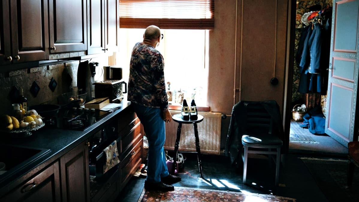 Remu Aaltonen katsoo ikkunasta ulos keittiössään.
