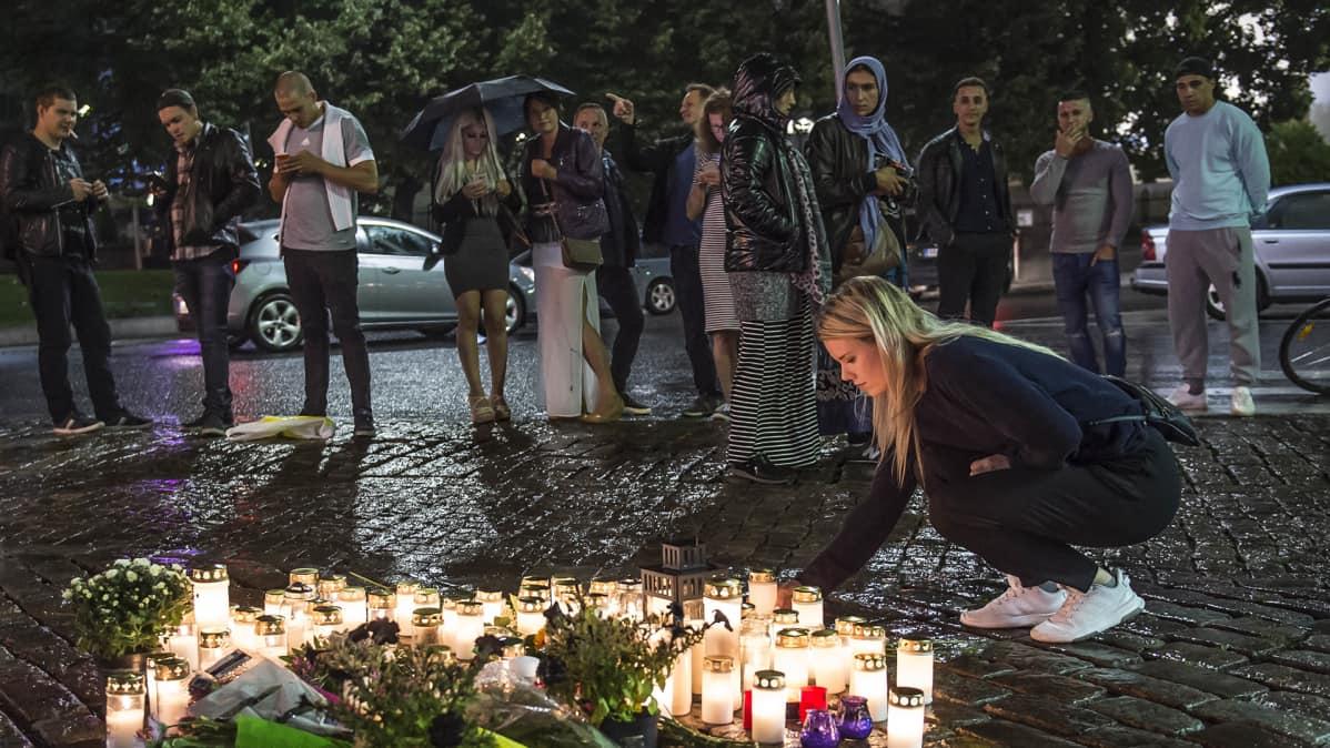 Ihmiset toivat kynttilöitä ja kukkia Turun puukotusten uhrien muistoksi Turun Kauppatorille perjantai-iltana 18. elokuuta.