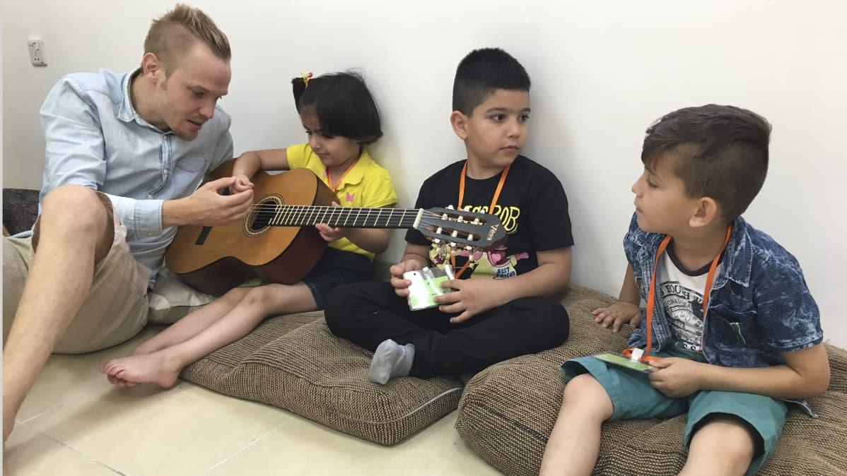 mies opettaa kitaran soittamista