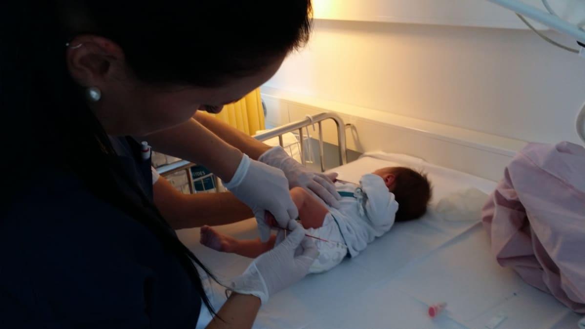 Laboratoriohoitaja Niina Vaitomaa ottaa vauvasta näytettä.