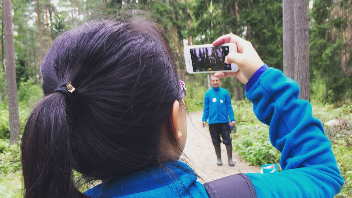 Nainen ottaa valokuvaa metsässä