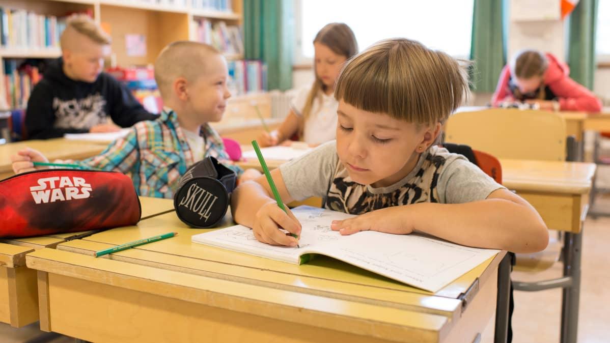 Kuvassa oppilaat opiskelevat koululuokassa