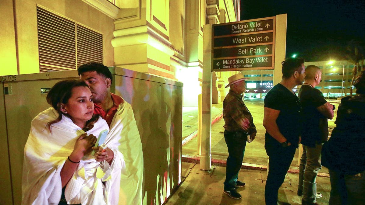 mies ja nainen seisovat öisen hotellin edustalla peittoon kääriytyneenä