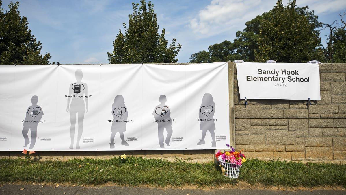 Kuolleiden muistoksi pystytetty juliste koulun ulkopuolella.