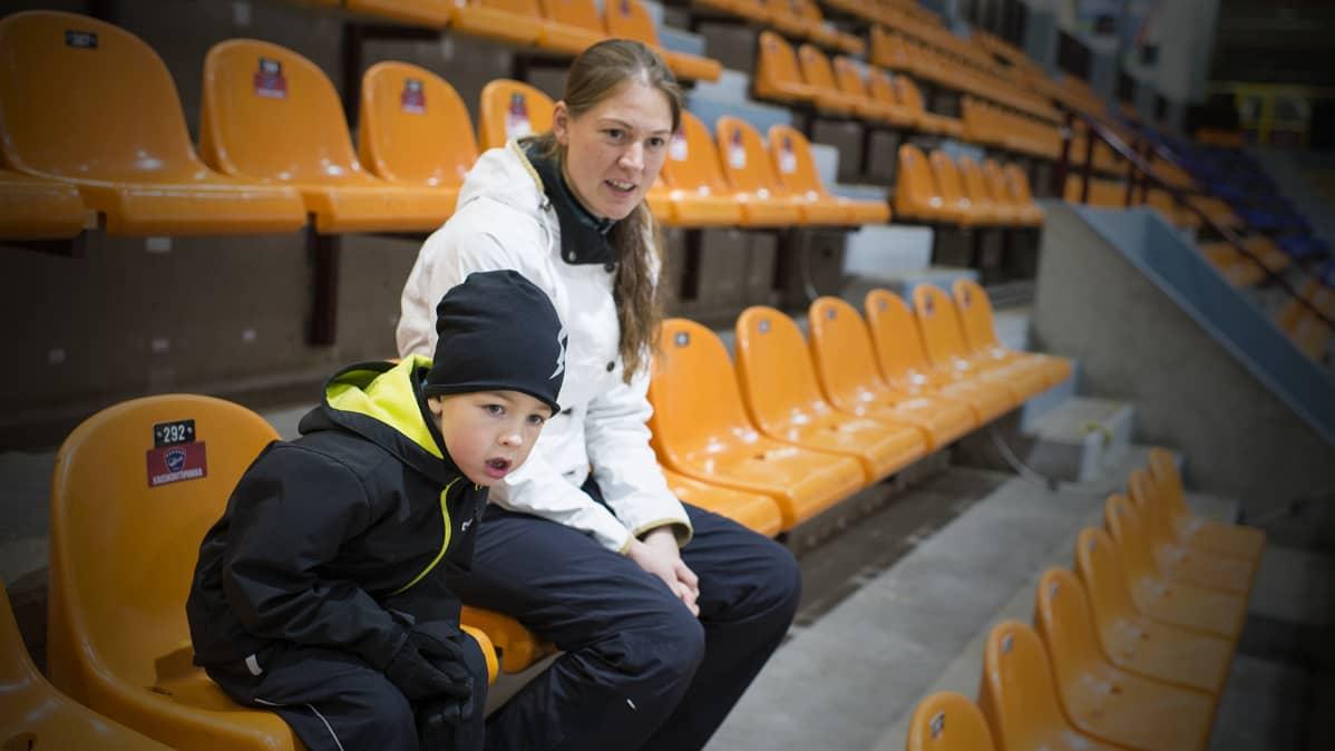 Jesper ja äiti jäähallin katsomossa.