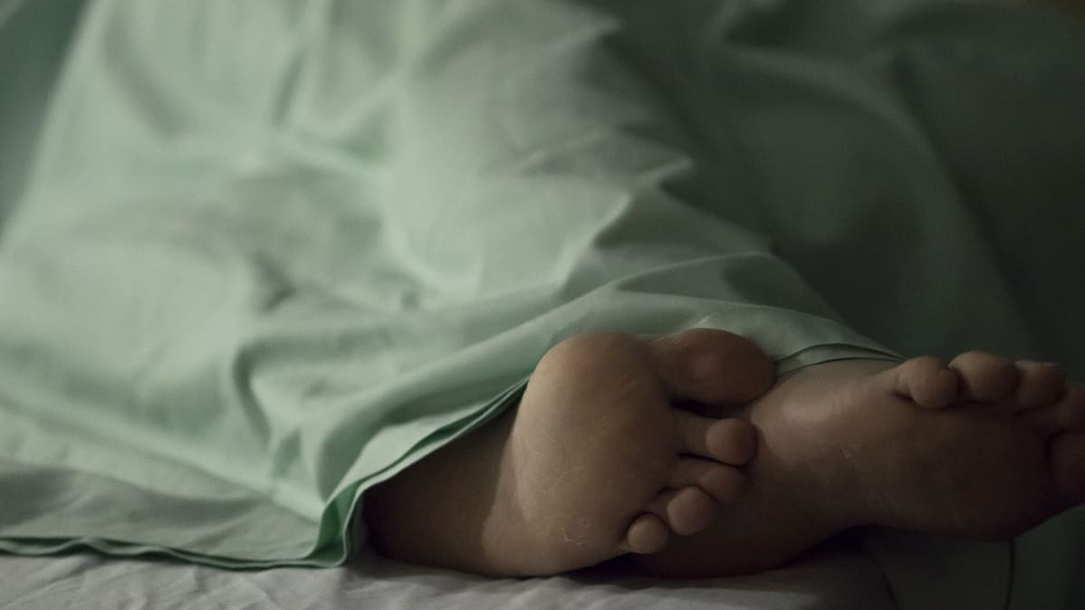 Nainen makaa potilasvuoteella sairaalassa.