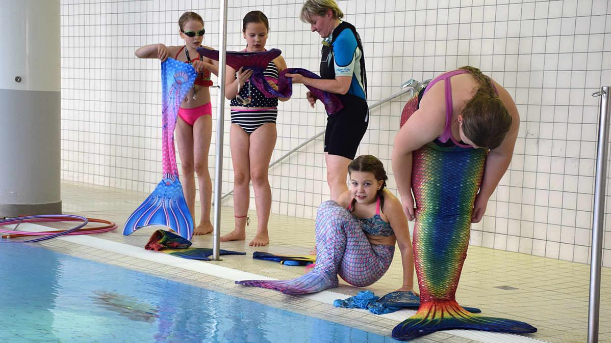 Tytöt pukevat merenneidon pyrstöjä uima-altaan reunalla
