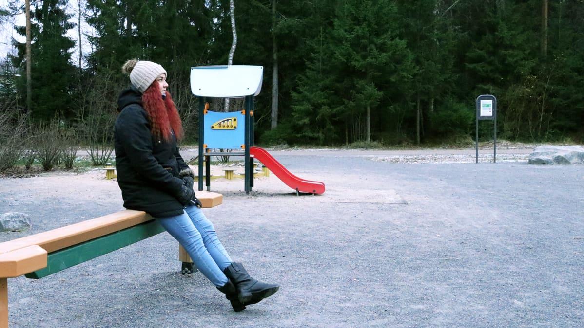 Nuori nainen istuu puistossa.