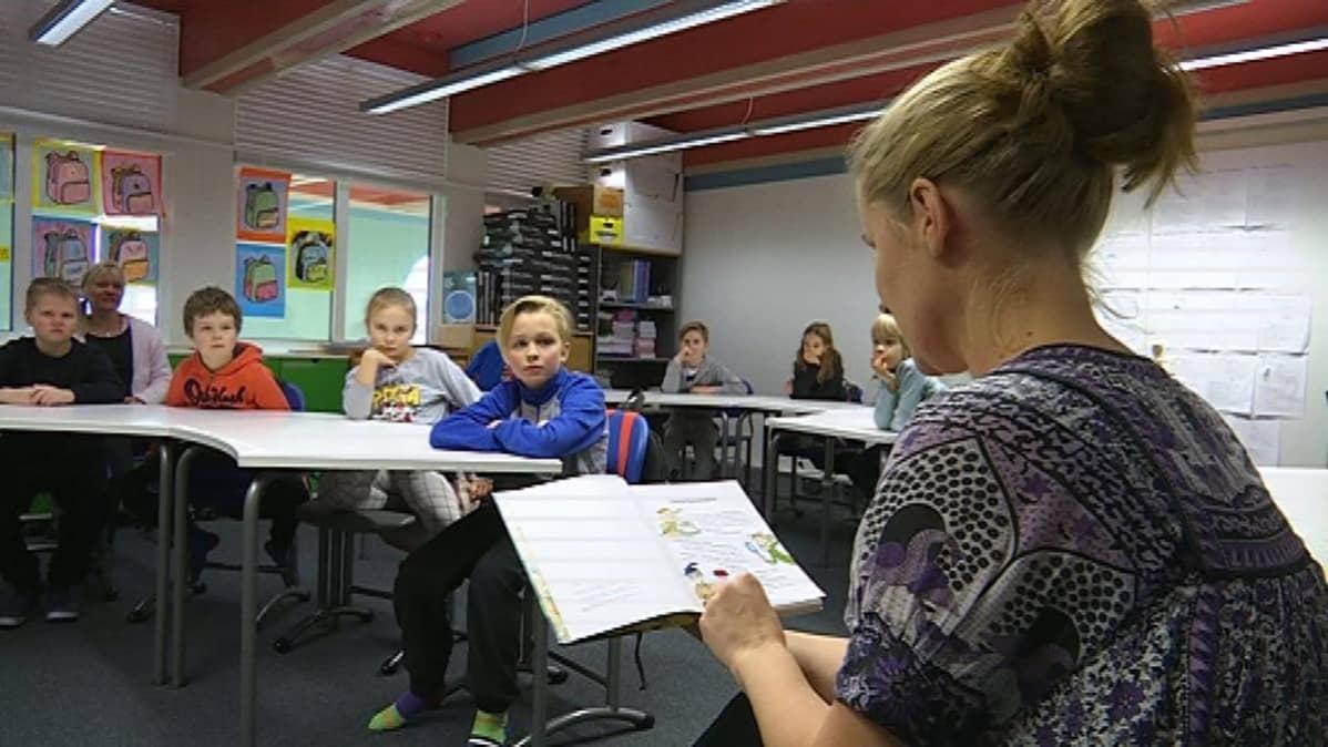 Opettaja lukee oppilaille