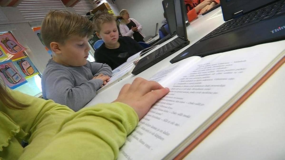 koululaiset lukevat luokassa kirjaa