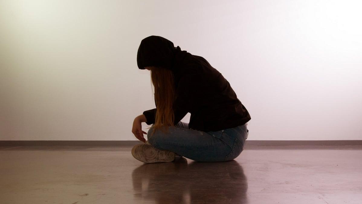 Mustaan huppariin ja farkkuihin pukeutunut nuori istuu pää painuksissa.