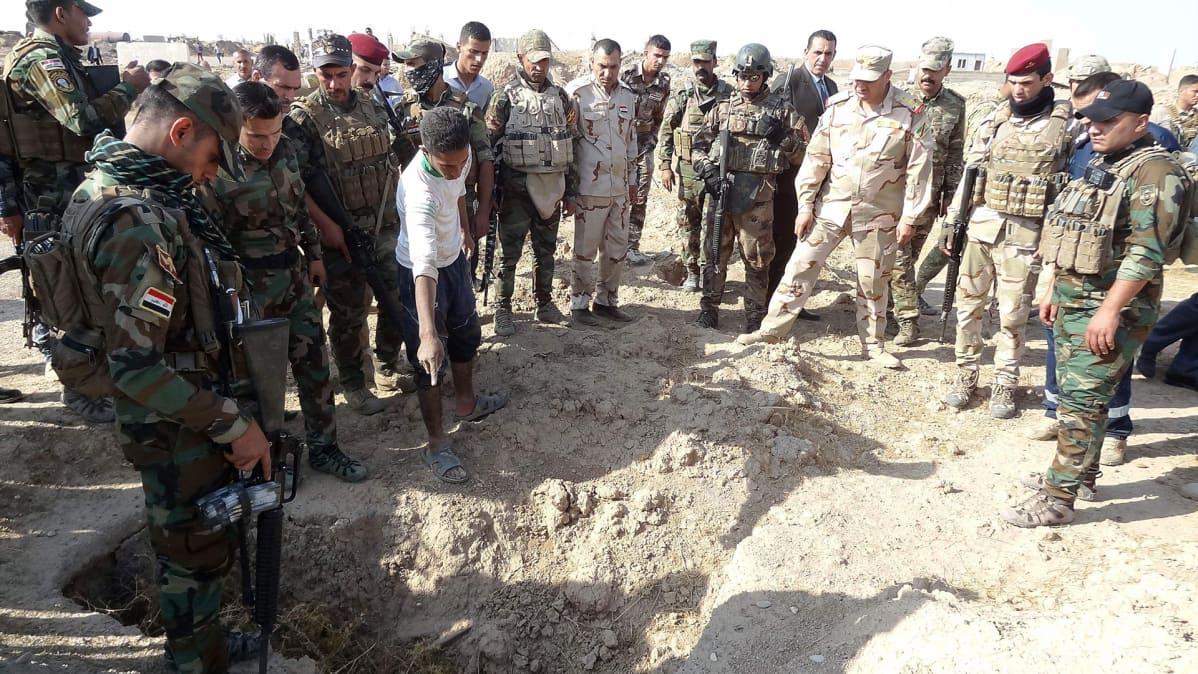 Irakilaisjoukkojen sotilaita Hawijan kaupungin lähistöllä sijaitsevan joukkohaudan äärellä Pohjois-Irakissa 11. marraskuuta.