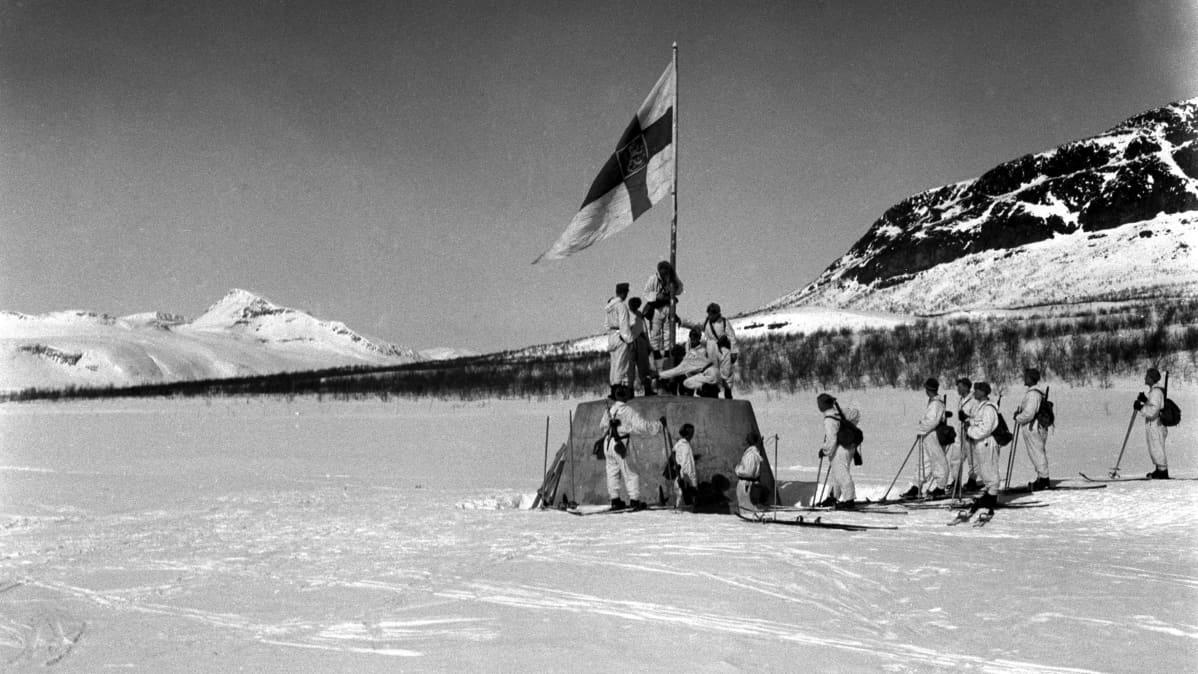Suomalaissotilaat nostavat lipun kolmen valtakunnan rajapyykille Lapin sodan päätyttyä 27.4.1945