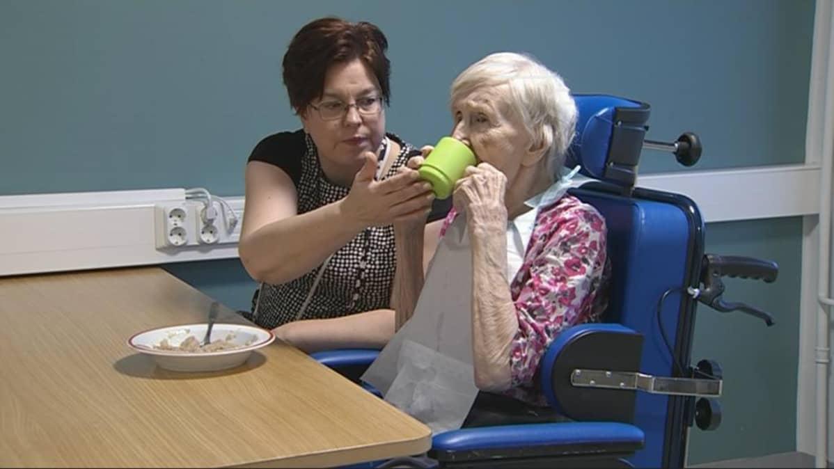 Vaahterakodin vastaava sairaanhoitaja Anu Timonen auttaa 95-vuotiasta Siiri Jauhiaista ruokapöydässä.