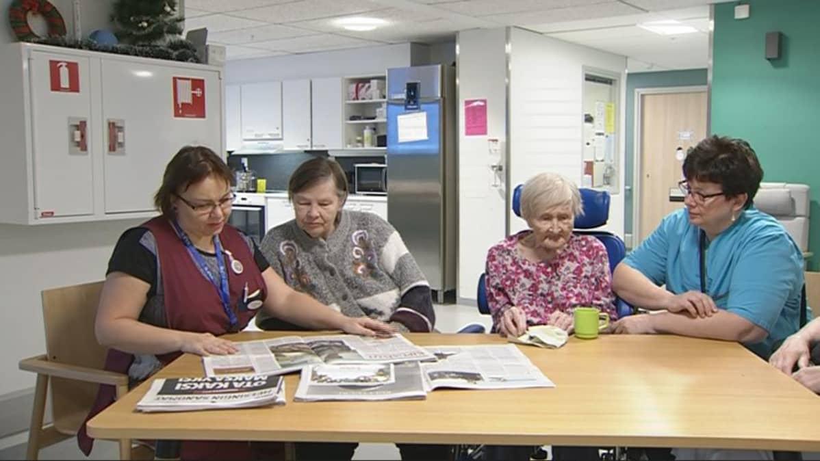 Kaksi hoitajaa lukee lehteä muistisairaille vanhuksille pöydän ääressä.