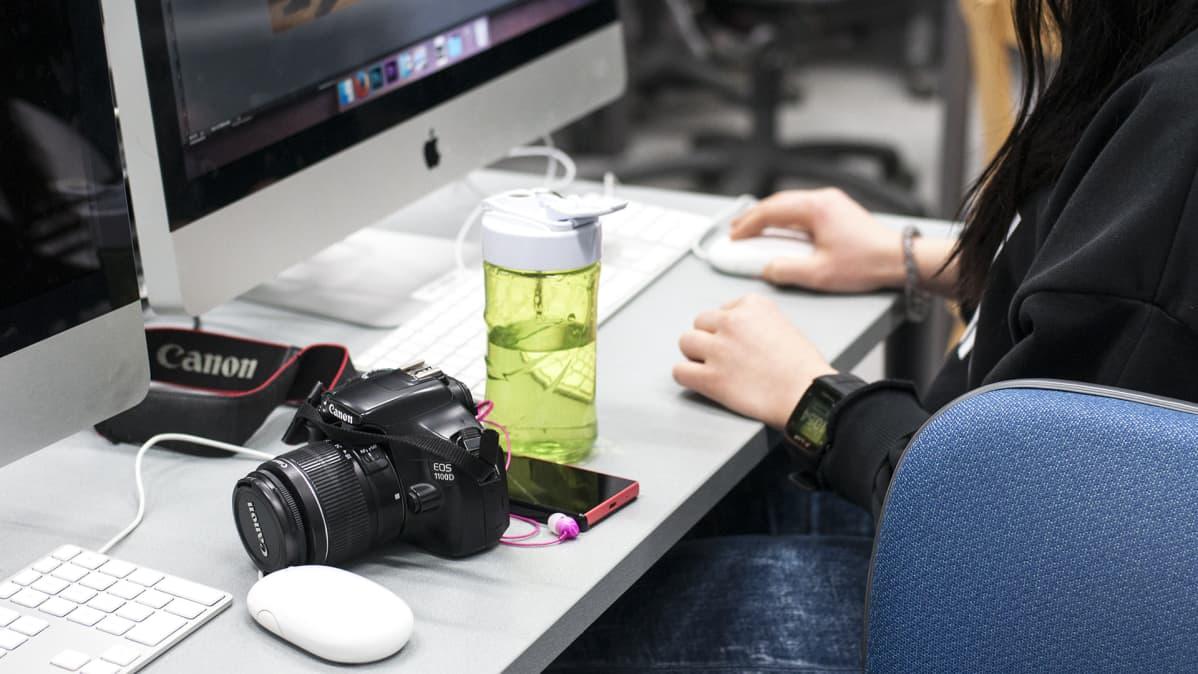 Jyväskylän ammattiopiston kuva-artesaaniopiskelija työskentelemässä tietokoneella