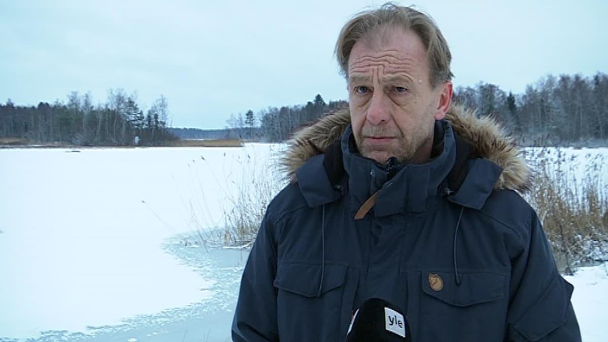 Mies seisoo järven ja mikrofonin välissä