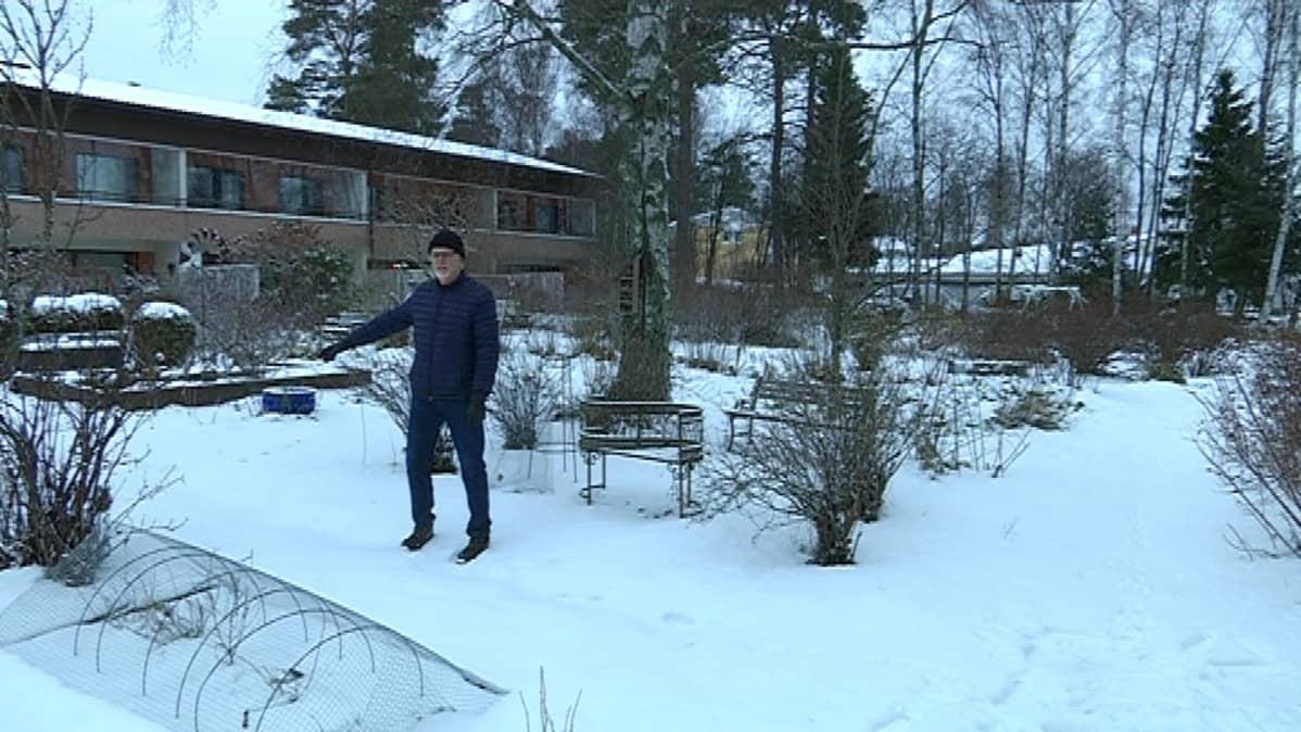 Mies seisoo pihallaan ja osoittaa lunta