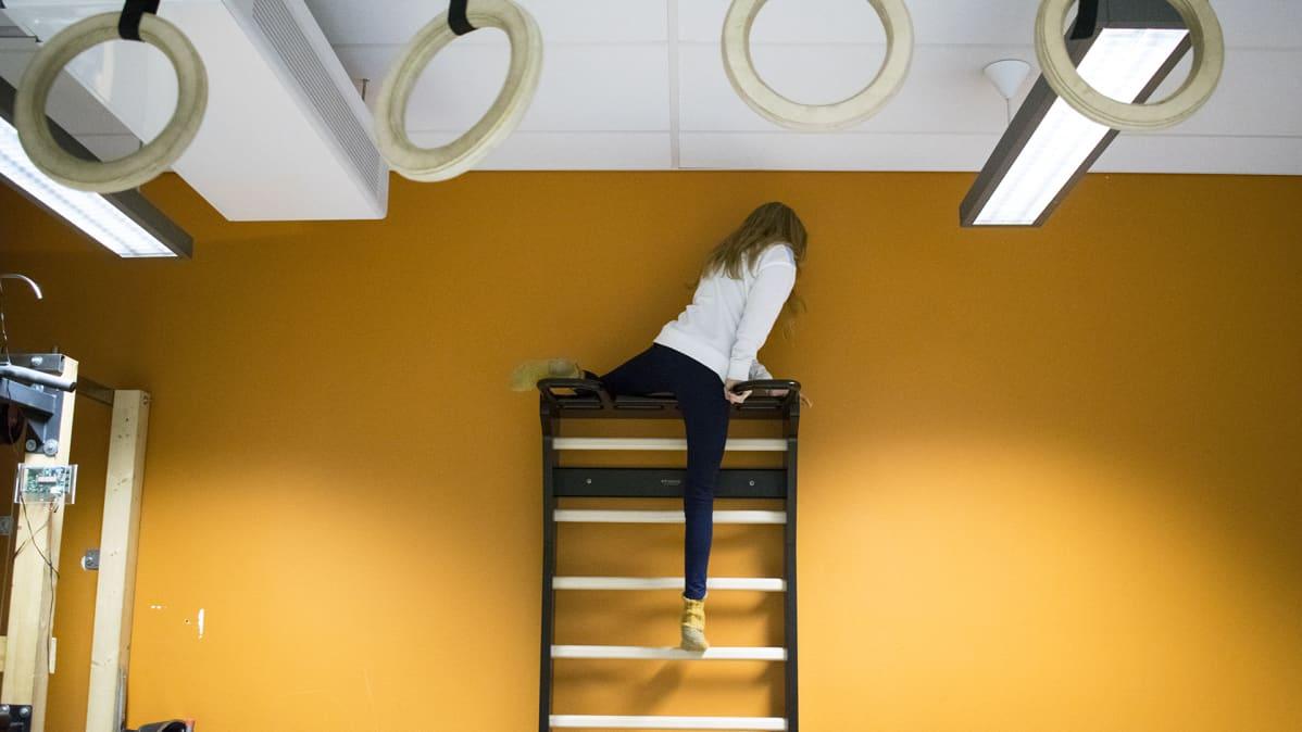 Jyväskylän kristillisen opiston oppillas kiipeilee luokkahuoneessa