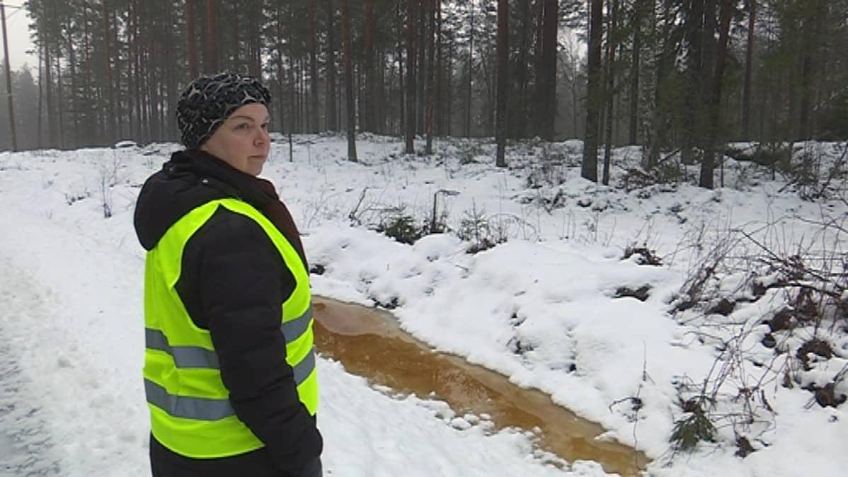 nainen, Tanja Mynttinen, tieisännöitsijä seisoo talvella vetisen ojan vierellä asivutien reunalla, yksityistiet