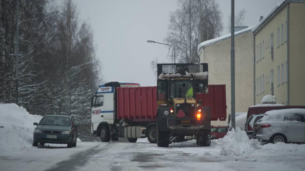 Työkone nostaa lunta kuorma-auton kyytiin.