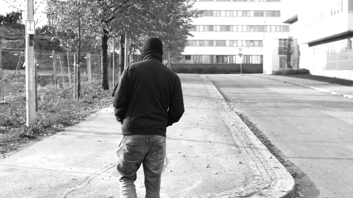 Mustavalkoinen kuva ihmisestä takaapäin.
