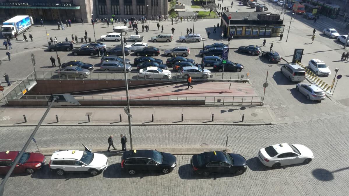 Bild tagen uppifrån på taxiområdet intill järnvägsstationen i Helsingfors. Flera taxibilar har samlats för en demonstration
