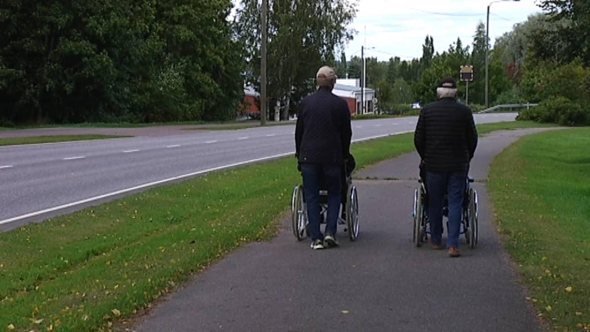 två personer skuffar rullstol